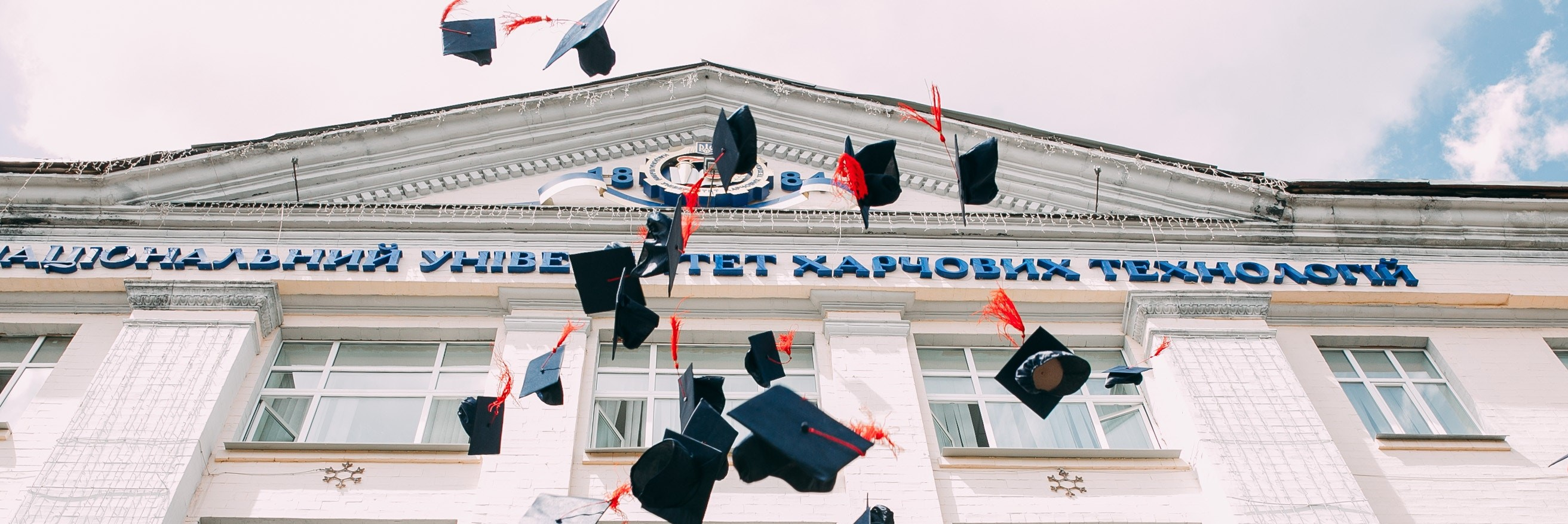 graduates throwing caps banner - vasily-koloda-620886-unsplash